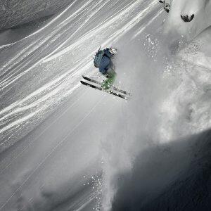 Skier doing a 360 jump over a powder slab
