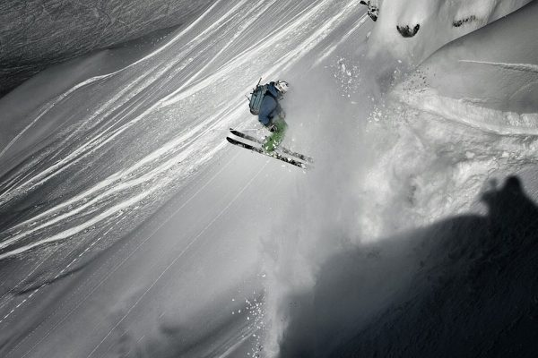 Skier doing a 360 jump over a powder slab