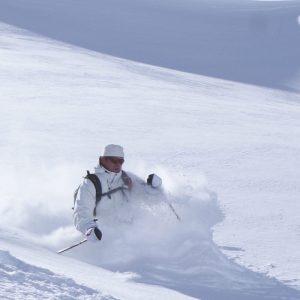 Skier doing short turns on powder