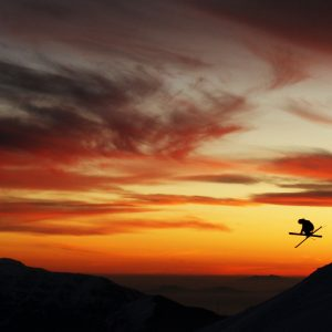 Skier jumping infront of a dramatic sunset