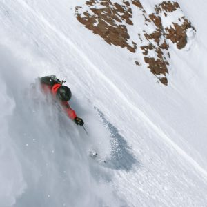Skier on powder snow afetr an heliski flight