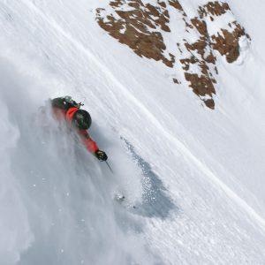 Skier on powder snow afetr an heliski flight
