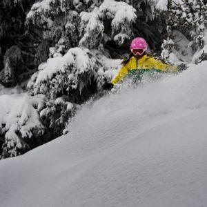 Young freeride skier sliding sideways on powder