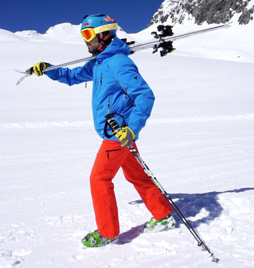 Ski instructor walking with skis on shoulder