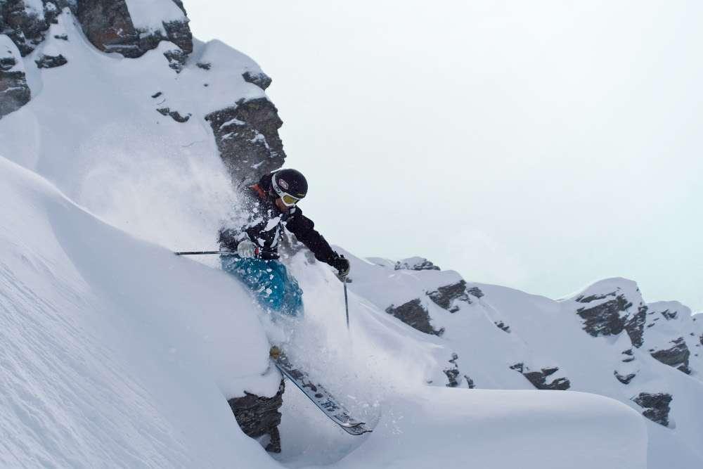 Freerider skiing over rocks in Verbier
