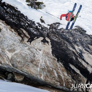 Skier jumps over a clift doing a 360