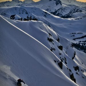 Freeride skier riding on the powder at sunset time