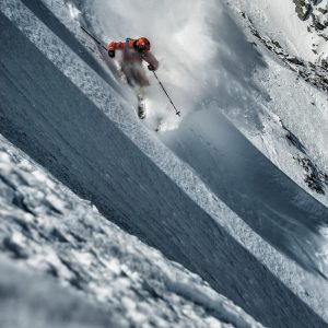 Freeride skier breaks the packed snow with a power turn in Verbier