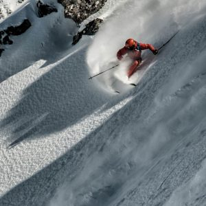 Freeride skier doing a sharp snap turn at Verbier mountains